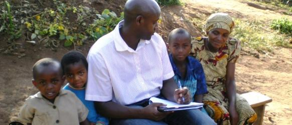 A Community Health Worker chats with a woman and children in Rwanda